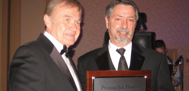 Marc Castillo, right, receives the Pioneer Award from NAPIM president George Sickinger.